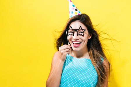 黄色の背景に紙パーティとパーティの帽子を持つ若い女性の棒します。