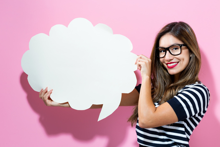 Young woman holding a speech bubble on a pink background Stockfoto