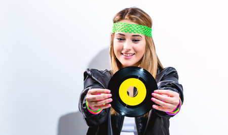 Woman with a vinyl record in 1980s fashion on a white background