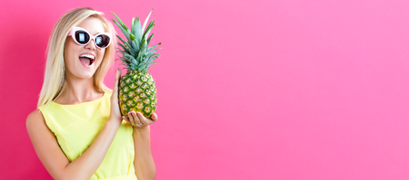 Happy young woman holding a pineapple on a pink background Stock Photo