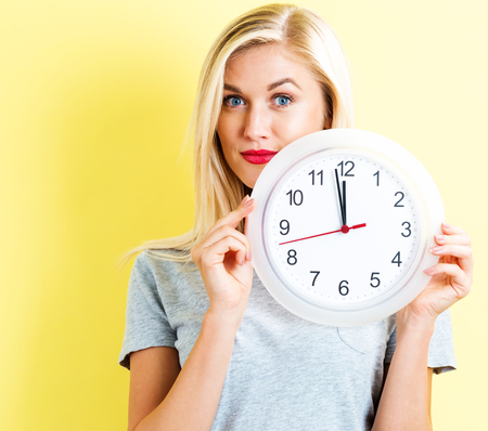 oclock: Young woman holding a clock showing nearly 12 Stock Photo