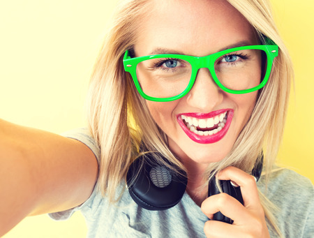 earbud: Happy young woman with headphones on a yellow background