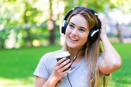 earbud: Young woman with headphones outside on a summer day