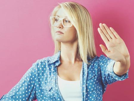 Jonge vrouw die een afwijzing stelt op een roze achtergrond