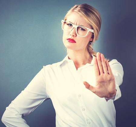 Jonge vrouw die een afwijzing pose op een grijze achtergrond Stockfoto
