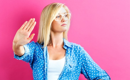 De jonge vrouw die een afwijzing vormt stelt op een roze achtergrond
