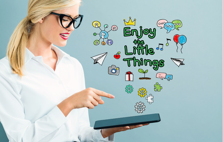 sayings: Enjoy The Little Things text with business woman using a tablet Stock Photo