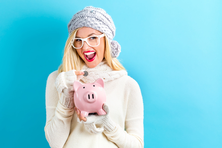 Young woman in winter clothes with a piggy bank Stockfoto