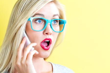 Jonge vrouw praten op de telefoon op een gele achtergrond Stockfoto