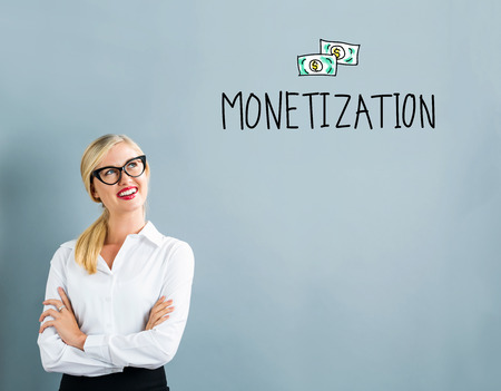 Monetization text with business woman on a gray background Stock Photo