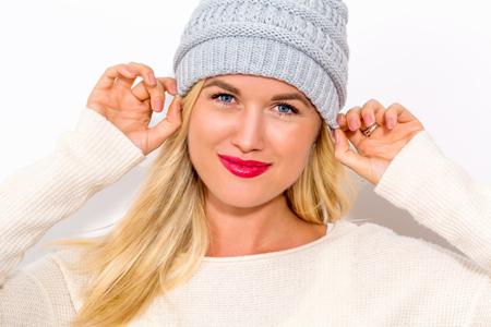 冬の白い背景の上の服で幸せな若い女
