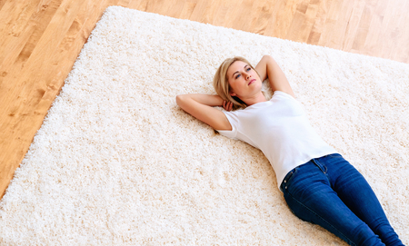 Young woman lying down on a carpet