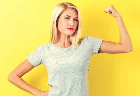 강력한 젊은 여자가 노란색 배경에