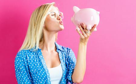 Junge Frau mit einem Sparschwein auf einem rosa Hintergrund Standard-Bild - 80976932
