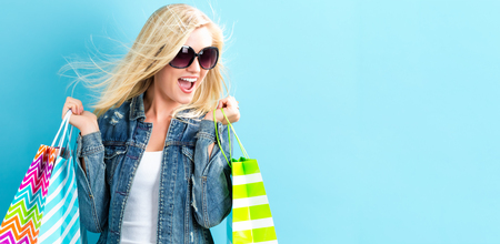 Happy young woman holding shopping bags on a blue background Standard-Bild
