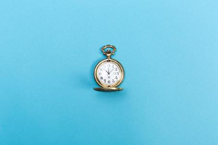 明るい青の背景に小さな黄金時計 写真素材