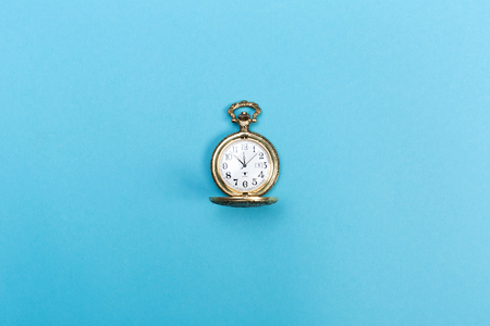 Kleine goldene Uhr auf einem hellblauen Hintergrund Standard-Bild - 80977085