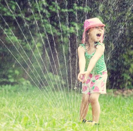 Het gelukkige peutermeisje spelen in een sproeier op een hete de zomerdag