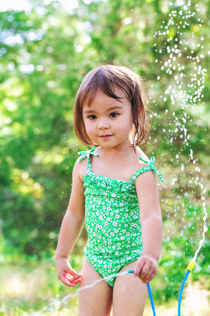 Happy toddler girl playing with sprinkler outside Stock Photo