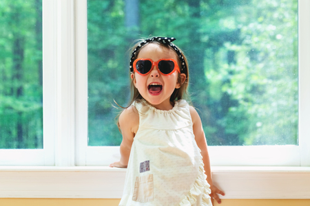 Happy toddler girl wearing sunglasses in her house Stock Photo