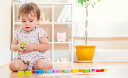 Cute toddler girl playing with her toys inside her house