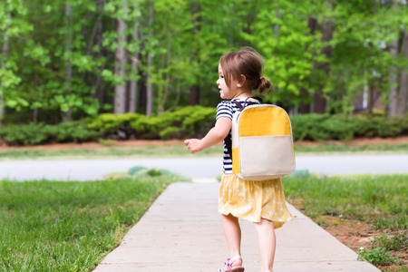 Toddler girl walking away from home on the sidewalk