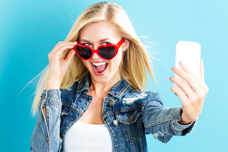 Young woman taking a selfie on a blue background Stock Photo
