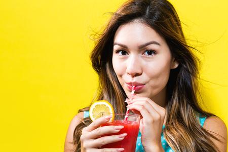 黄色の背景に幸せな若い女飲料スムージー