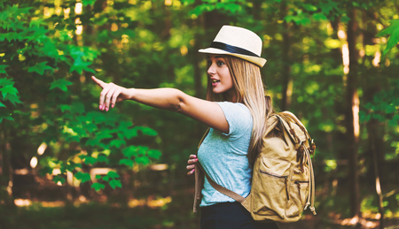 seeking: Young woman in the forest with a backpack and hat