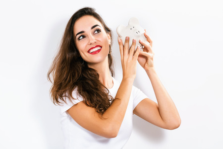 Happy woman holding a piggy bank on a white background