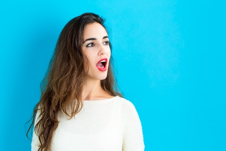 word of mouth: Profile of a young woman on a blue background