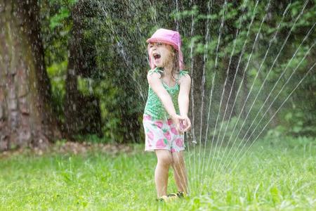 더운 여름날에 스프링 클러에서 놀고있는 행복한 유아 소녀