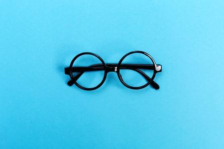밝은 파란색 배경에 라운드 안경의 쌍