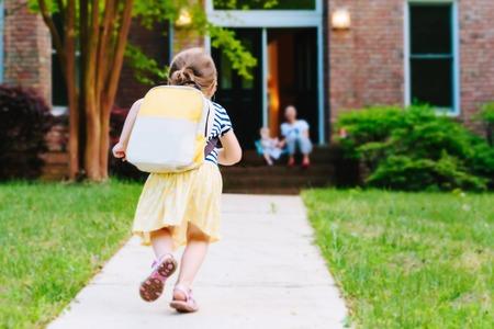 Ragazza del bambino felice che arriva a casa dalla scuola con uno zaino Archivio Fotografico - 81384575
