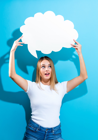 Young woman holding a speech bubble on a blue background Stok Fotoğraf
