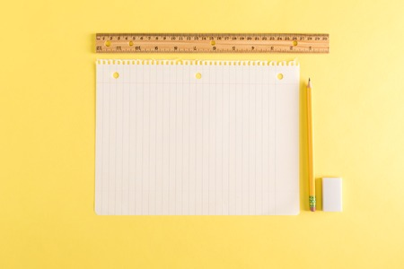 Ruler and a blank sheet of notebook paper on a yellow background