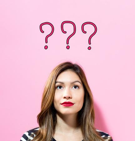 ピンクの背景の若い女性と疑問符本文 写真素材