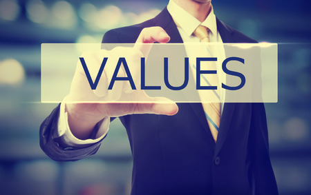core strategy: Values text with Businessman on blurred abstract background