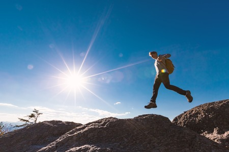 산 하이킹 갭을 뛰어 넘는 남자 스톡 콘텐츠