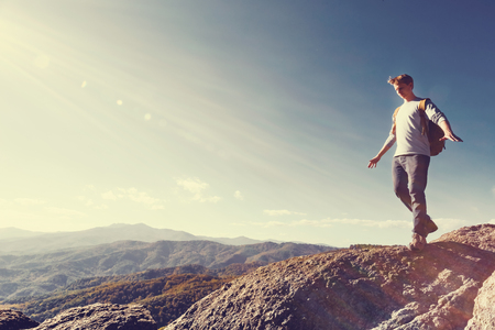 ledge: Man walking on the edge of a cliff high above the mountains Stock Photo