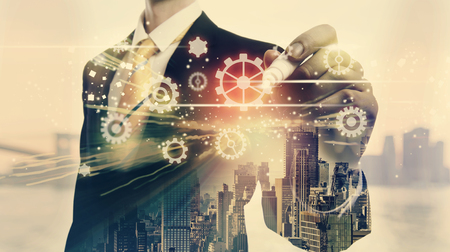 double exposure: Gears with double exposure of businessman and big city Stock Photo