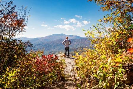 아래 산을 내려다 보는 절벽의 가장자리에있는 남자
