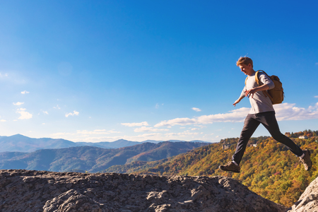 ledge: Man jumping over a gap high up on a mountain hike Stock Photo