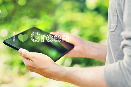 I Love Green concept with young man holding his tablet computer outside in the park
