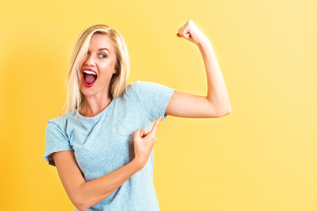 Powerful young woman on a yellow background Stock Photo
