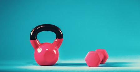 Pink kettlebell and dumbbell on a blue gradient background Stock Photo