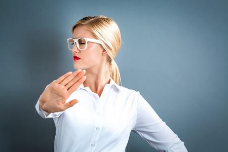 De jonge vrouw die een afwijzing vormt stelt op een grijze achtergrond