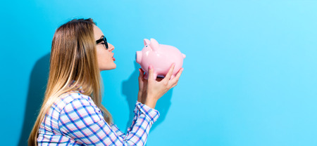 Happy woman holding a piggy bank on a blue background Stock Photo