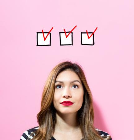 ピンクの背景の若い女性とチェックリスト 写真素材