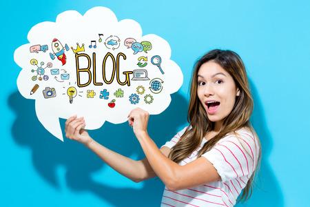 青い背景の吹き出しを保持している若い女性のブログのテキスト 写真素材